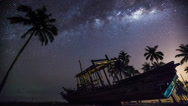 Stock Video Footage of Milkyway timelapse  with ship wreckage and palm tree - Pan Down