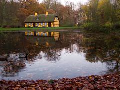 Yellow half timbered house at lake Stock Photos