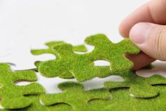 hand holding a green puzzle piece, green concept - stock photo