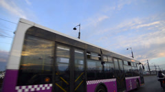 Three purple city, municipal, public bus sequence vehicle, passing fast bridge Stock Footage