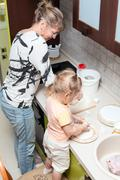 Small child helping mother to cook in domestic kitchen Stock Photos