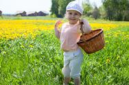 Stock Photo of small happy caucasian girl standing on meadow with basket