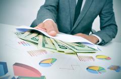 man giving an envelope full of dollar bills - stock photo
