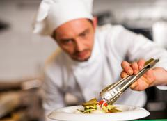 Chef arranging tossed salad in a white bowl Stock Photos