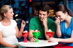 Three friends enjoying tempting dessert Stock Photos