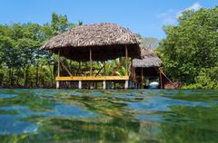 Tropical hut with thatch roof from water surface Stock Photos