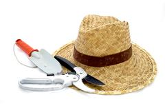 Straw hat and hand trowel and pruning shear on white Stock Photos