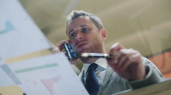 Businessman talking on cellphone and reading documents HD Stock Footage