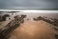 long exposure landscape beach scene with moody sky - stock photo