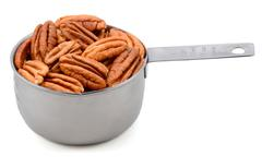 Whole pecan nuts in a metal cup measure Stock Photos