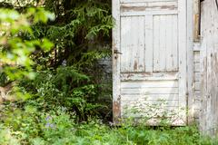 Open door of abandoned wooden house in the forest - stock photo
