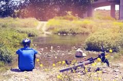 Cyclist getting some rest at the riverside with a retro filter effect Stock Photos