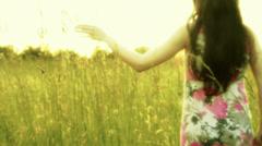 Woman in a field with long dress walking Stock Footage