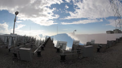 Mirrors reflecting blue sky and fluffy clouds at solar power plant Stock Footage