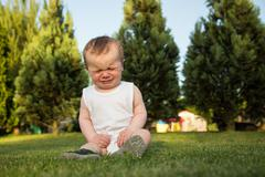 Baby boy sits on a grass and cries - stock photo