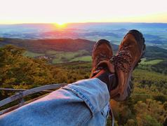 Two tired legs in blue jeans and brown leather boots with sunset at horizo Stock Photos