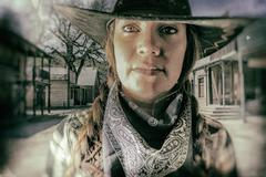 Old West Cowgirl Eyes Western Town - stock photo