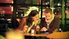 Couple watching photos on tablet computer in bar HD - stock footage