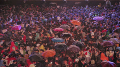 Crowd under the rain watching rock concert in Rome: umbrella, dancing, music Stock Footage