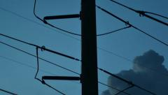Silhouette of public electricity system with clouds moving behind Stock Footage