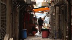 Caucasian man walks down backstreet alley Stock Footage