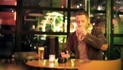 Young man with smartphone drinking beer in bar late at night HD Stock Footage