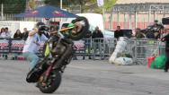 Stock Video Footage of stunt man zooming with motorcycle: acrobatics show in the street