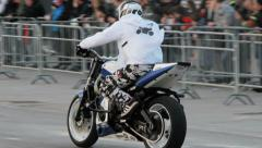 Stunt man zooming and drifting standing on the motorcycle Stock Footage