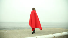 Lonely girl in red blanket looking at the sea. HD with motorized slider. 1080p. Stock Footage