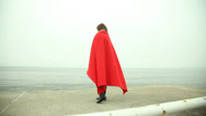 Stock Video Footage of Lonely girl in red blanket looking at the sea. HD with motorized slider. 1080p.