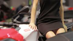 Cute and sexy hostess ride motorcycle with miniskirt during exhibition Stock Footage
