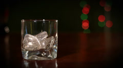 Pouring whiskey into a glass with ice cubes Stock Footage
