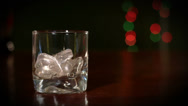 Stock Video Footage of Pouring whiskey into a glass with ice cubes