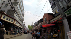 POV driving Pudong  narrow streets shops Shanghai China Stock Footage