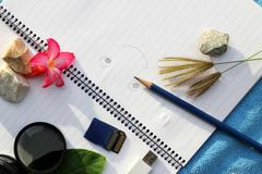accessories for travel. key car and lens memory card for camera have a notebook - stock photo