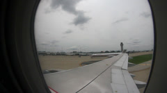 Window view over wing of airplane taxing to gate Stock Footage