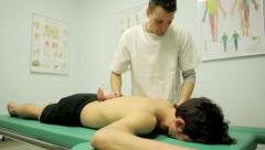 chiropractor is manipulating shoulder and back of a young patient in his surgery - stock footage