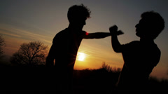 Silhouettes of two fighters on gold sunset background: martial art, fight Stock Footage