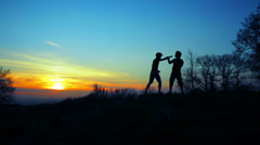 Silhouettes of two fighters on blue sunset fiery background: martial art, fight - stock footage