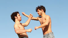 Two athletes try martial arts moves: outdoor, mountain, fighting, training Stock Footage