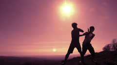 Back sunlight Silhouettes of fighters traing martial art moves, fighting  Stock Footage