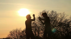Silhouettes of two fighters on sunset smooth background: martial art, fight - stock footage