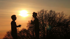 Silhouettes of two fighter greet each other and starting fighting on sunset Stock Footage