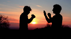 Silhouettes of two fighters on sunset fiery background: martial art, fight - stock footage