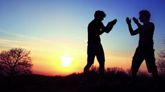 Silhouettes of two fighters on orange sunset background: martial art, fight - stock footage