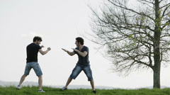 two athletes try martial arts moves: outdoor, mountain, fighting, training - stock footage