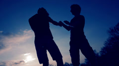 Silhouettes of two fighters in sky background while training: martial art, fight - stock footage