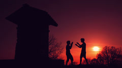 Silhouettes of two fighters on sunset red fiery background: martial art, fight Stock Footage