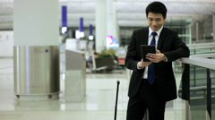 Asian Chinese Businessman Airport Global Travel Mini Tablet Communication Stock Footage