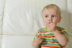 Boy eating sweets Stock Photos